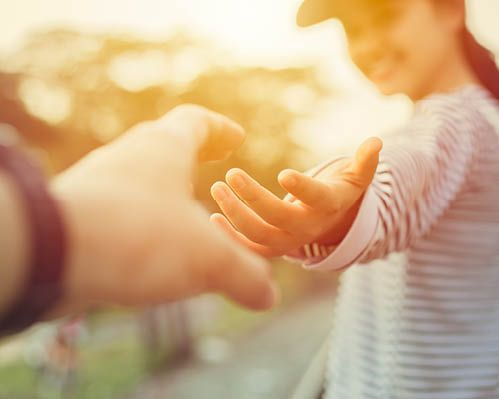 Mental Coach lehrt Familienhilfe und reicht die Hand einem jungen Mädchen.