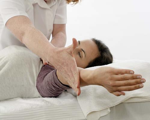 Schülerin der Touch for Health Ausbildung kräftigt Muskeln am Klienten