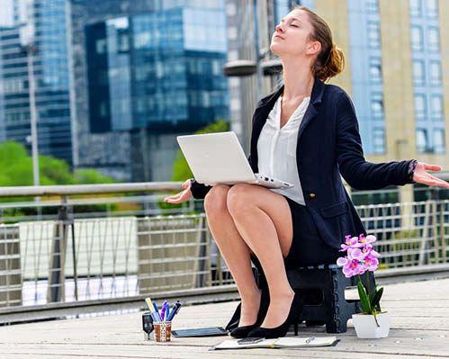 Geschäftsfrau macht Achtsamkeitsübungen im Büroalltag