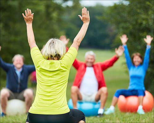 An der Weiterbildung Erlebnispädagogik trainieren Senioren in der Natur mit einem Gymnastikball.